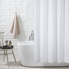 Modern Bathroom With White Painted Brick Freestanding Bathtub And Shower Curtain