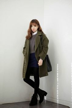 Oversized coat over a jumper and shorts ensemble, wearing black stockings and boots