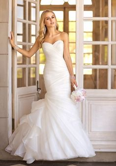 This trumpet designer bridal gown features asymmetrical Organza pleats throughout its beautiful bodice and skirt, while fun and flirty gathered fabric on the side hints at vintage charm.