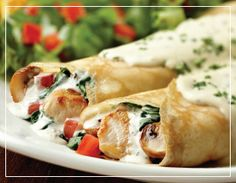 Mimi's Roasted Chicken Crepe with mushrooms, spinach and tomatoes, sauteed with brie cheese and asiago sauce.