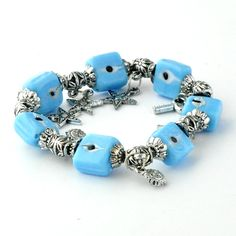 An elasticated bracelet featuring light blue square shaped ornaments and silver charms. Specially handcrafted in Izmir, Turkey.