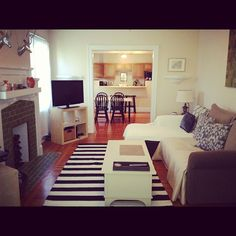 Small but cute white and black apartment. Kitchen in background