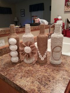 Pinterest ideas are dangerous! This gorgeous project cost me less than $8! Cover old liquor or wine bottles with twine, spray paint 2 of them white, and decorate the outside to spell a word of your choice! Love it!