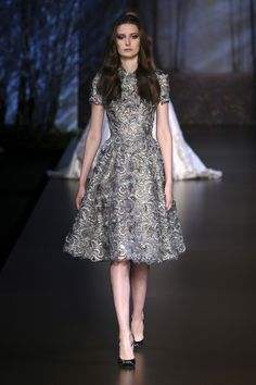 Metallic gunmetal guipure lace flared dress with three dimensional elements and metallic feather appliqué.