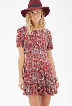 Burgundy tribal print dress. Fluted bottom. Orange and Olive accents. Scoopneck collar. Back zipper.