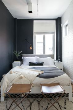 Bedroom with dark walls, light bedding, and a sconce