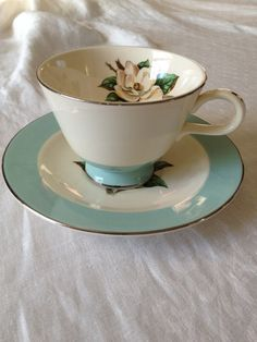 Turquoise-trimmed tea cup and saucer with a magnolia.