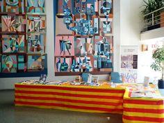 """Preparant la paradeta de Sant Jordi al vestíbul de la biblioteca, amb la reproducció dels """"Murals d'aigües"""" d'Antoni Rovira Brull  de fons."""