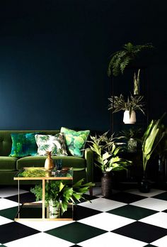 A striking example of using plants as art, this room forgoes wall décor completely and opts for a corner of verdant green instead. (The velvet green sofa and black-and-white checkered...