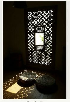 window with musharabih wood screen that plays with the light adding its patterns