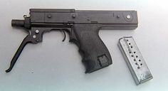 The second MPA with the 15-round magazine removed and the trigger guard extended to act as a forward grip.