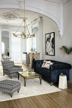 Living room with classic architectural details a blue velvet upholstered couch, and a low-hanging gold chandelier. Interior Design For Living Room Living Room Interior, Home Living Room, Living Room Designs, Classic Living Room, Apartment Living, Interior Livingroom, Art Deco Living Room, Living Area, Vintage Modern Living Room
