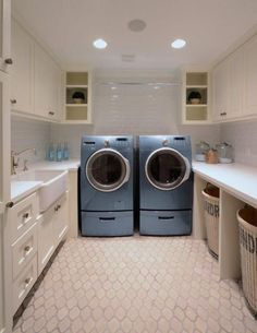 Laundry Room Design. U-shaped laundry room has ivory cabinets with white quartz countertops and subway tiled backsplash atop an arabesque tile floor. Over the blue front-load washer and dryer is a tension rod.