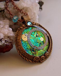 """Second groups of pendents made using Holo Effect from Blue Bottle Tree. Love the aged victoian/ steampunk look around the holo """"gem"""" glowing from within. A larger pendent which houses watch faceand gears."""