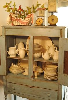 love this little green cabinet..perfect for holding white ironstone...