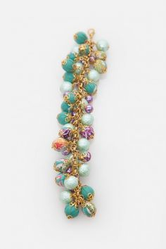 Gelang dengan model tumpukan mutiara bungkus batik hijau dan mutiara ungu yang dihiasi rantai emas dari Ego. Material mutiara dan batik. Size: One Size.Diameter 8cm.