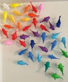 wall of rainbow origami koi - DIY wall hanging instructions (sort of - no actual origami instructions included).