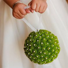 This whimsical green pomander—constructed with button chrysanthemums, chiffon and pearl pins—is super light-weight, making it just the thing for your flower girl to carry down the aisle, Grant Avenue Florist, grantaveflorist.com.