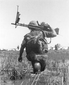 Marines crossing a rice paddy while on patrol, holding an M-60 machine gun, Vietnam, 1966.