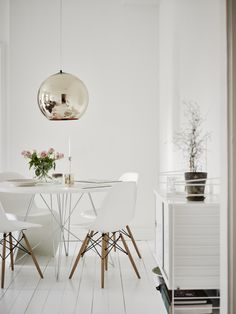 Clever use of space - Hege in France white dining room eames chairs panton, round dining table gold pendant light string shelves green plant
