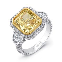 A superb cushion-cut fancy yellow diamond weighing 5.23 carats is the central focus of this dazzling three-stone engagement ring, which exudes Deco inspiration; the center is bordered by a lining of 18K yellow gold and a delicate halo of micropave diamonds before being flanked by 2 shield-cut white diamond side stones; a view of the side profile reveals more round brilliants engulfing the ring; from Uneek's Natureal Collection<br />