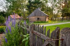 A rustic picket fence and some spring flowers add foreground interest to compliment the log structure.