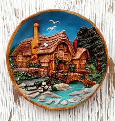 This colorful decorative ceramic plate has a high relief image of a rustic cottage nestled in the trees along a riverbank with its own private bridge and lush landscaping. The bright blue of the sky and the rich aqua of the river make the straw colored cottage come to life. Wonderful textures on the thatched roof and red tile chimney. This piece is in great condition with no cracks or chips, and only some minor wear to the paint.  11.5 inch diameter  2 inch deep  Hook on back, ready to hang…