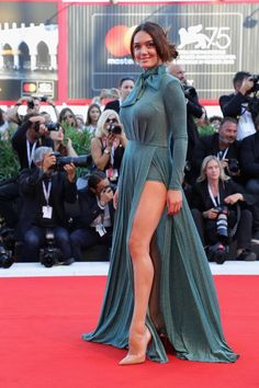Italian dancer Klaudia Pepa walked the red carpet before the screening of 'Vox Lux' wearing a high-neck, floor-length green dress with two thigh splits. The gown featured a large bow at the neck and Pepa paired the dress with nude heels. Nice Dresses, Formal Dresses, Wedding Dresses, Naomi Watts, Nude Heels, Opening Ceremony, Lady Gaga, Green Dress, Film Festival