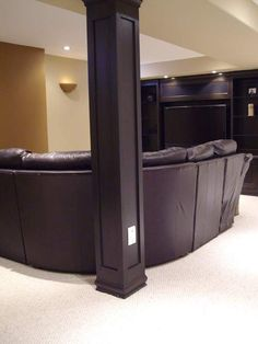 Trimming out the basement support posts is a fairly inexpensive way to add design to your basement and can be easily incorporated into your layout as part of a bar, or to hang wireless speakers for surround.