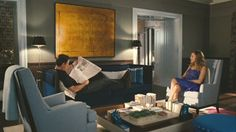 """website for Movie Set Houses ==Carrie and Big's living room includes a sofa by Montauk Sofa upholstered in blue wool-mohair from Donghia and a pair of beige midcentury side chairs. The bright floral Birdie Blossom Cushion by Paul Smith for the Rug Company adds a classic """"Carrie"""" touch. (Source: Elle Decor.)"""