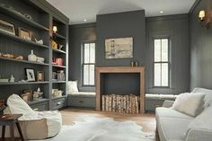 Chic gray den is equipped with a charcoal gray faux fireplace complemented with a wood mantel and birch wood decor.