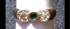 Hübscher Strass-Ring aus den 1940iger Jahren, Metall vergoldet(Amerikaner gestempelt), in der Mitte ist ein grüner Strass-Stein eingelassen, Größe 0,10 ct.  auf der Acht sind 10 kleine, farblose...