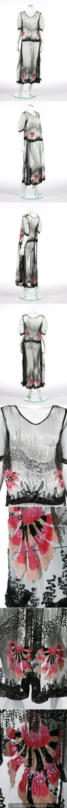 A beaded tulle cocktail dress, circa 1915-20. adorned with zig-zagged steel beads, vermicular black sequins and large pink carnation palmettes, with beaded rope belt which slots through and ties over one hip, pointed side panels edged in beaded tassels. KTA