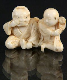 A NETSUKE Japan, 19th century Two sitting men, ivory, carved, 3cm high.