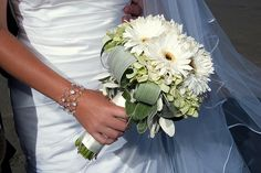 Angel's Blossoms bouquet - White Gerberas are known to represent purity which are paired thoughtfully with white hydrangea. The soft greenery in the background and the white satin stems complete this look that gives off a heavenly vibe. This is a classy choice for a bridal bouquet.  Bouquet Contents: Gerbera, Hydrangea, Salal, Aspidistra Leaves - $65