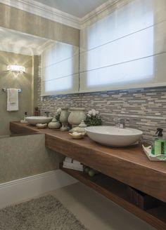 O lavabo ganhou bancada em madeira de demolição. Pastilhas revestem a parede principal.