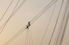 March 29, 2012. Men work on power transmission lines in Tezpur, India.