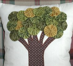 Green and gold yo yos make up the crown of this appliqued tree. The pillow is made from cotton fabric with polyfill stuffing. It measures 11 x 13.