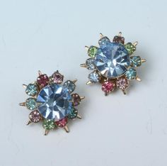 Pretty pair of vintage clip on style earrings have a center of blue surrounded by pastel colors in a starburst look. Measure 3/4 inches across. Great vintage condition. To view more photos or to purchase please see this link