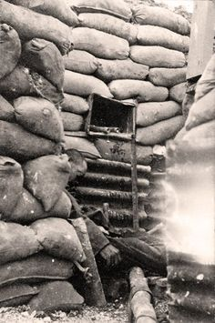 Battle of the Somme. A German sentry lies dead in the trenches at Thiepval, the day after capture. Above him, top right, is a trench periscope still in position while lower down two German stick grenades sit in a box. - Lt Patrick Koekkoek by kind permission of Patricia and Michael Brock.
