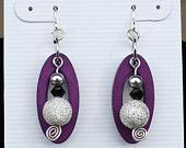 Dangle earrings w/ sparkly silver stardust bead, small black crystal & metal bead hanging in front of deep purple oval w/ silver fish hooks.