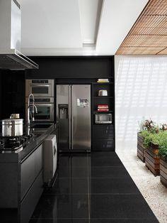 El espacio, diseño del estudio, conecta con un patio acristalado, cuya luz contrasta con el granito y el mobiliario, todo en negro.