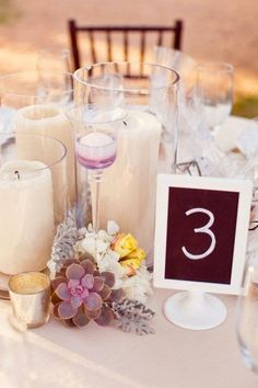 Other tables will have low trios of pillar candles in cylinder vases surrounded by clusters of cream hydrangeas, blush spray roses, and purple succulents with tall fluted votives and low fluted votives. www.stemfloral.com I www.halforangephotography.com