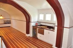 Upstairs Family room is reminiscent of a ship's hull, the Nautical theme is carried over to the Mahogany and Maple flooring, Brass light fixtures, and built-in Bar, Seating.