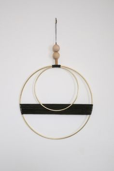 "Beautiful brass and waxed cord wall hanging with raw wood and vintage brass bead detail. Measurements: - Larger brass circle is 10"" - Smaller brass circle is 6"" - Beaded hanger above circles is 6"" - T More"