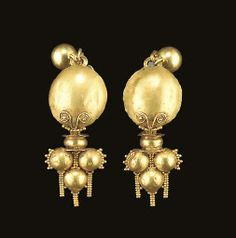 A PAIR OF ROMAN GOLD EARRINGS Circa 2nd-3rd Century A.D. Each with a hoop of two spiral twisted wires and a plain wire tapering to a single wire at each end and formed into a hook and eye closure, a sheet dome mounted on the hoop, adorned at the base with a row of granulation and a filigree double spiral, with a fixed pendant of three hollow spheres attached to the hoop by an intermediate reel-shaped collar, the spheres ornamented with a fringe and rigid chains of granulation; a modern ear…