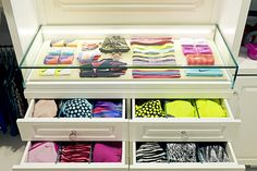 Glass case with white drawers full of athletic clothes
