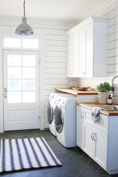 Laundry/mud room with ship lap wall detail, white cabinetry and wood countertops. The door with large window and transom lets the light in.