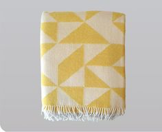 Twist a Twill Blanket in Yellow  Tina Ratzer's cozy Twist a Twill blankets are made in Denmark from 100% pure new wool. Their graphic and striking design was inspired by the triangular shapes noticeable in traditional twill patterns.    -51 x 74 inches $139.00
