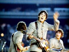 Paul waves to fans during a concert at Shea Stadium - The Beatles